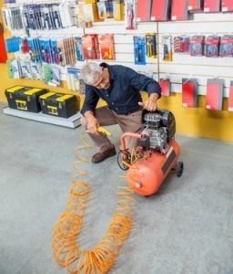Senior Man Examining Air Compressor In Shop